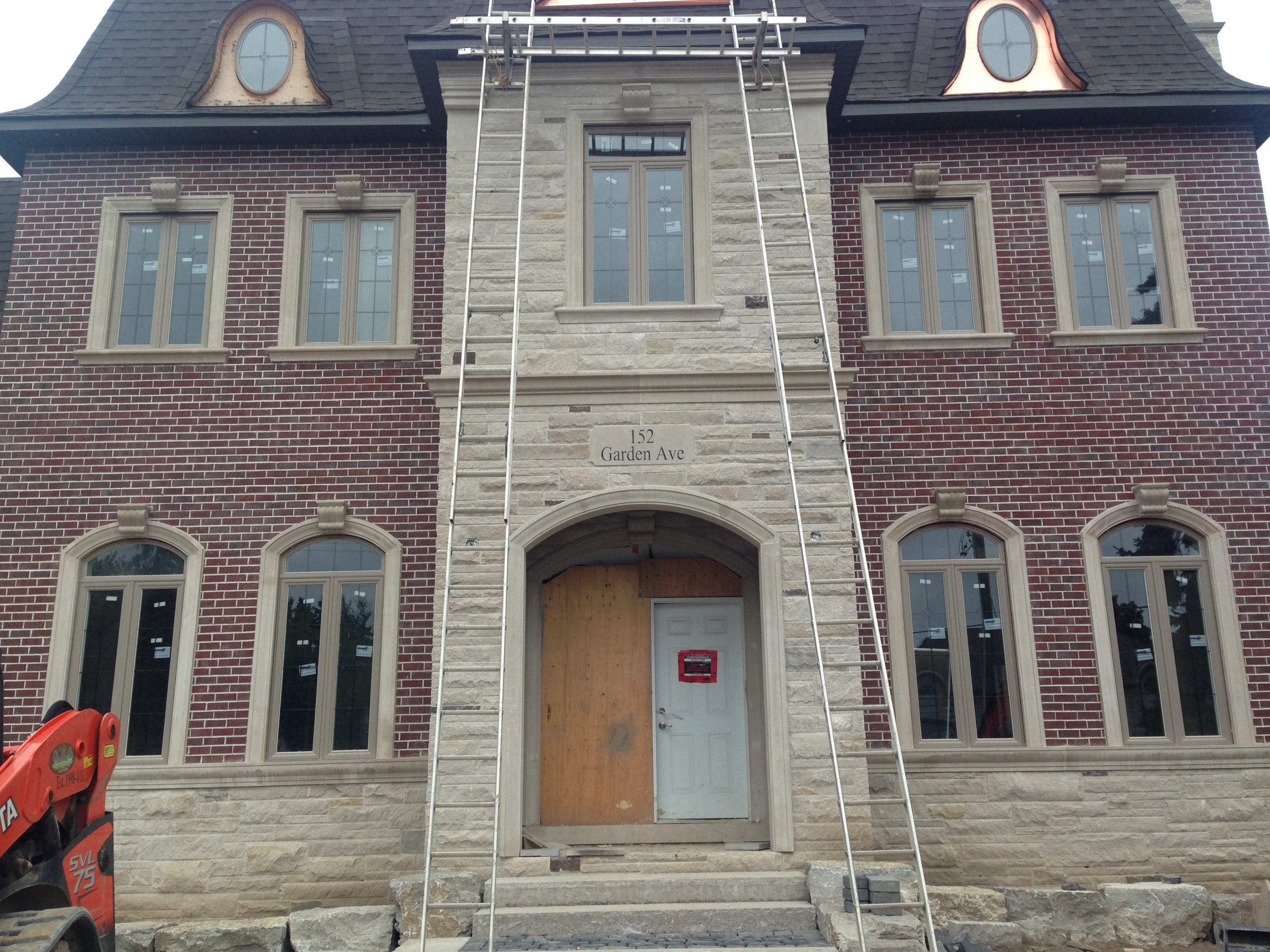 Photo of the front of a custom home with brick walls and a natural stone entrance and skirt